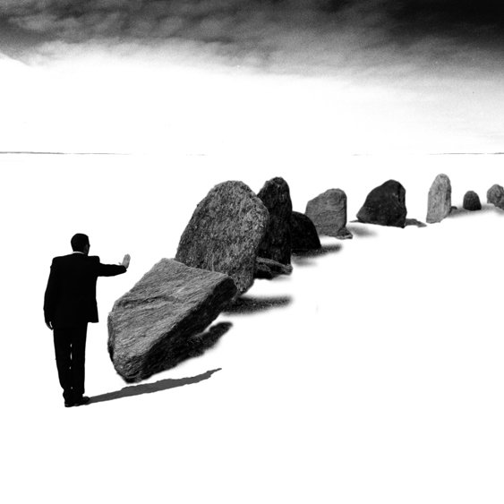 Homme en tailleur poussant des blocs de roche alignés