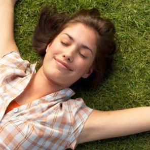 Femme souriant allongée dans l'herbe les yeux fermés