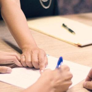 Mains prenant des notes sur une table de réunion