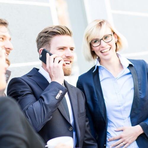 Homme lumineux au téléphone au milieu de ses collègues