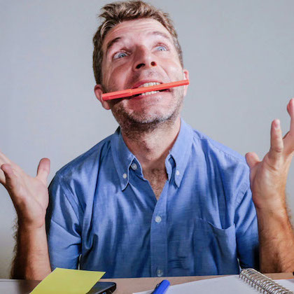 Homme énervé en train de mordre son crayon au travail