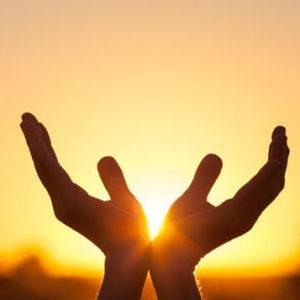 Deux main côté à côté levées au ciel vers le soleil