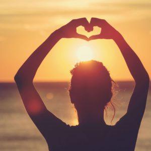Profil au couché de soleil symbolisant un cœur avec ses deux mains