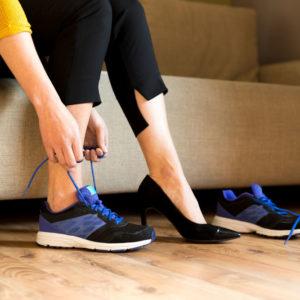 Femme chaussant ses baskets au lieu des talons hauts